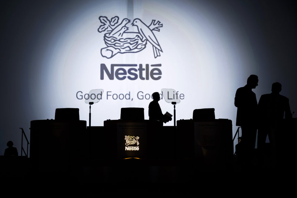 The Nestle SA logo sits on display behind the stage ahead of the company's annual general meeting (AGM) in Lausanne, Switzerland, on Thursday, April 11, 2012. Nestle SA's chairman said Switzerland is becoming more difficult as a business location after voters last month approved some of the world's toughest limits on executives' pay. Photographer: Valentin Flauraud/Bloomberg via Getty Images