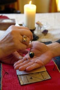 Eine Hellseherin hält einen Pendel über die Hand einer Kundin, 9. Januar 2006. (Keystone/Sandro Campardo)