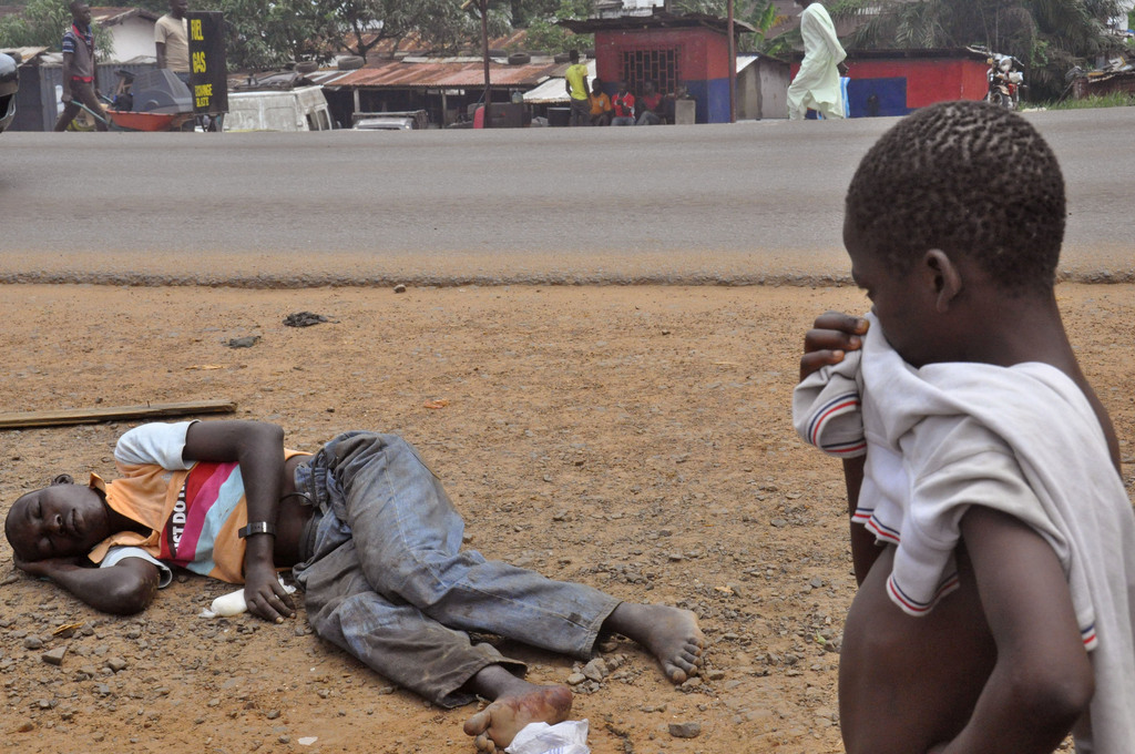 Ein Kind betrachtet einen an Ebola erkrankten Mann in Monrivoa, Liberia. Foto: Abbas Dulleh (Keystone)