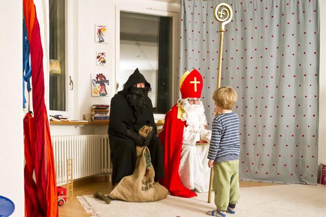 Ein Kind spricht zum Samichlaus mit Schmutzli der Chlausgruppe St. Otmar am Montag, 6. Dezember 2010 in St Gallen. (KEYSTONE/Ennio Leanza)
