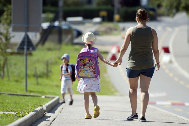 Melissa et Andreas accompagnes de leur fille au pair devant une ecole a Echallens, ce mardi 16 aout 2011. La rentre scolaire aura lieu le lundi 22 aout dans le canton de Vaud. (KEYSTONE/Dominic Favre)