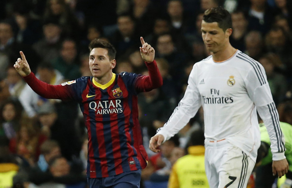 Barcelona's Lionel Messi (L) celebrates a goal next to Real Madrid's Cristiano Ronaldo during La Liga's second 'Clasico' soccer match of the season at Santiago Bernabeu stadium in Madrid March 23, 2014. REUTERS/Paul Hanna (SPAIN - Tags: SPORT SOCCER TPX IMAGES OF THE DAY) - RTR3IAYQ