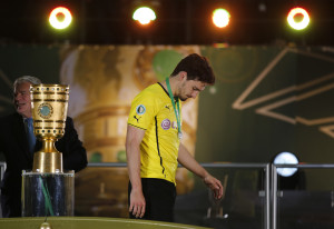 Borussia Dortmund's Mats Hummels (R) walks past the trophy next to German president Joachim Gauck after his team's German Cup (DFB Pokal) final soccer match against Bayern Munich in Berlin May 17, 2014. REUTERS/Ina Fassbender (GERMANY - Tags: SPORT SOCCER TPX IMAGES OF THE DAY) DFB RULES PROHIBIT USE IN MMS SERVICES VIA HANDHELD DEVICES UNTIL TWO HOURS AFTER A MATCH AND ANY USAGE ON INTERNET OR ONLINE MEDIA SIMULATING VIDEO FOOTAGE DURING THE MATCH. - RTR3PMT2