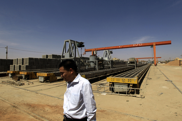 A Chinese man walks at Shanghai Hui Bo Investment Co (SHIC) for manufacturing railway cement sleepers and accessories in north Khartoum February 14, 2013. Sudan should become a transport route for some of South Sudan's oil production once the two countries can agree an arrangement.Work to renew the rail tracks started last year when China's Shanghai Hui Bo Investment Co (SHIC) opened a plant in north Khartoum, opposite the Sudanese capital's main train station, and is producing 1,200 concrete sleepers a day, according to its Sudanese manager Sharaf Nasser. Picture taken February 14, 2013. To match Feature SUDAN-RAILWAY/ REUTERS/Mohamed Nureldin Abdallah (SUDAN - Tags: POLITICS TRANSPORT BUSINESS) - RTR3E106
