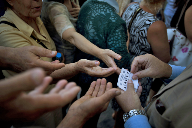 A bank employee distributes queue tags to elderly people waiting to enter a bank where they can pick up a per-person maximum of 120 euros ($134) for the week in central Athens, in this photo dated Monday, July 13, 2015. The latest incarnation of Greece's economic crisis over the span of a month saw Greece in the end accept harsh austerity measures from creditors to save the country from bankruptcy and possibly ignominiously getting kicked out of the eurozone. (AP Photo/Emilio Morenatti)