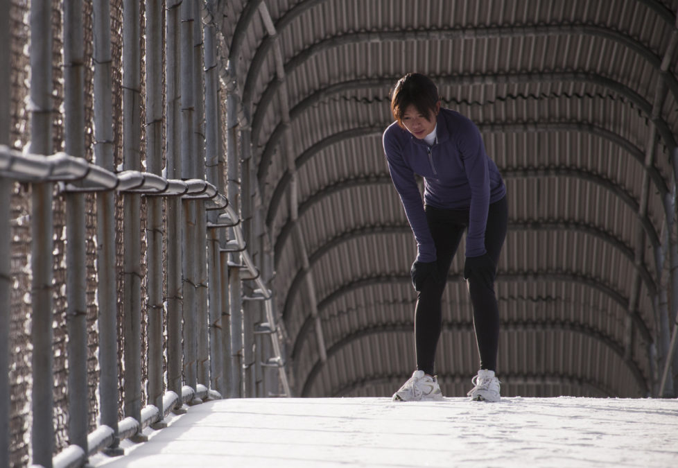 Sue Tran stretching before a snowy run in Salt Lake city, Utah.