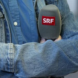 Ein Mikro eines SRF-Journalisten, fotografiert waehrend einer Medienkonferenz des Fussballverbandes in Feusisberg am Dienstag, 6. Oktober 2015. Die Schweizerische Radio- und Fernsehgesellschaft SRG plant den Abbau von rund 250 Stellen, wie sie am Dienstag in einem Communique mitteilte. Damit reagiert sie auf Einsparungen von 40 Mio. Franken, die ab 2016 anfallen. Als Grund werden die wegbleibende Mehrwertsteuer sowie der hoehere Gebuehrenanteil fuer Privatsender angegeben. Das Sparprogramm betreffe alle Sprachregionen und Unternehmensbereiche und erfolge vorrangig in Verwaltung, Informatik und Produktion. (KEYSTONE/Anthony Anex)
