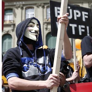 Demonstranten mit Guy-Fawkes- und Edward-Snoden-Masken protestieren gegen das Bundesgesetz betreffend die Ueberwachung des Post- und Fernmeldeverkehrs (BUEPF) am Samstag, 31. Mai 2014 auf dem Bundesplatz in Bern. (KEYSTONE/Peter Klaunzer)