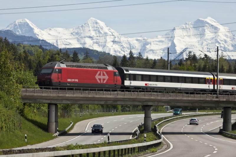 Niemand will die Kostenwahrheit im Verkehr: Bahn und Autobahn vor Schweizer Bergkulisse. Foto: Gaetan Bally (Keystone)