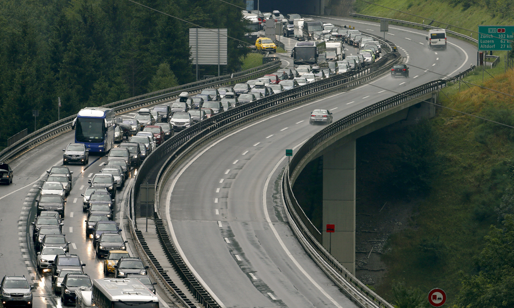 Vehicles travelling south wait in what local radio said was a more than 10 kilometre (6.2 miles) traffic jam on the northern side of the 17 kilometre (10.5 miles)-long St. Gotthard Tunnel near the central Swiss village of Wassen August 1, 2015. REUTERS/Arnd Wiegmann - RTX1MNBS