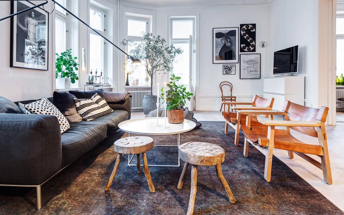 Im Wohnzimmer Dominiert Eine Sitzinsel Bestehend Aus Einem Modernen Kubischen Dunkelgrauen Sofa Zwei Ledersesseln Rustikalen Hockern Und Leichten