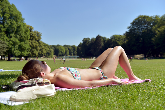 A woman sun bathes in a park during a heat wave in Brussels, June 30, 2015. Temperatures in Belgium are expected to reach 36 degrees Celsius, according to weather forecaster from the Belgian Royal Institute of Meteorology. REUTERS/Eric Vidal - RTX1IH1U