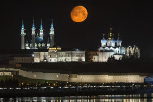 The full moon rises over the illuminated Kazan Kremlin with the Qol Sharif mosque, left, and The Transfiguration Cathedral, right, in Kazan, the capital of Tatarstan, located in Russia's Volga River area about 700 km (450 miles) east of Moscow, early Wednesday, July, 29, 2015. (AP Photo/Denis Tyrin)