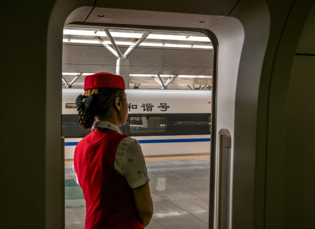 YICHANG, HUBEI PROVINCE, CHINA - 2015/09/27: A steward stands at the gate of a CRH train carriage. The first high-speed railway project in the United States with Chinese investment involved is expected to start as early as September 2016. (Photo by Zhang Peng/LightRocket via Getty Images)