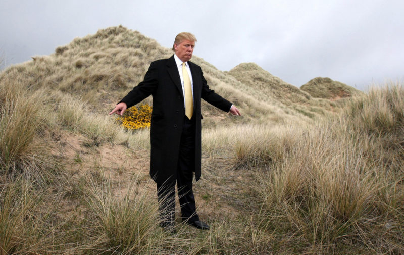 US billionaire Donald Trump gestures in the sand dunes of the Menie Estate, on the Aberdeenshire coast, Scotland Thursday May 27, 2010, the location of his planned $1.5 billion Scottish golf resort. Protesters opposed to Trump's planned luxury resort say they've pulled a trick shot out of their bag. At the center of the plan is local fisherman Michael Forbes, who has long been an irritant to Trump. Forbes has refused the American tycoon's offer of nearly $700,000 (488,000 pounds) to buy his family's 23-acre run-down farm, which sits at the center of the planned resort. But Forbes has sold an acre of his land near Aberdeen to protesters who also disagree with Trump's plans _ a sale which will force the property tycoon to face down more than 60 people. (AP Photo/Andrew Milligan/PA Wire) ** UNITED KINGDOM OUT NO SALES NO ARCHIVE **