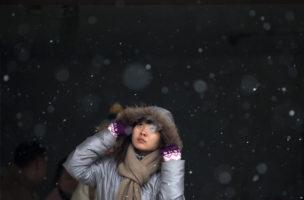 Sicher ist sicher: Eine Passantin kommt in Peking aus der U-Bahn und blickt in den Himmel. Foto: Andy Wong (AP)