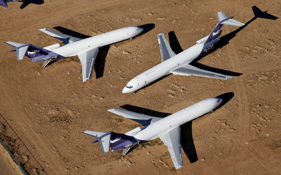Old airplanes, including Boeing 747-400s, are stored in the desert in Victorville, California March 13, 2015. Last year, there were zero orders placed by commercial airlines for new Boeing 747s or Airbus A380s, reflecting a fundamental shift in the industry toward smaller, twin-engine planes. Smaller planes cost less to fly than the stately, four-engine jumbos, which can carry as many as 525 passengers. Picture taken March 13, 2015. To match Insight AEROSPACE-JUMBO    REUTERS/Lucy Nicholson