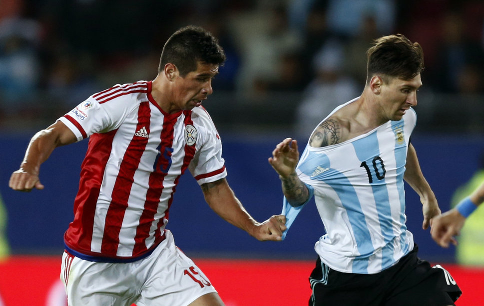 Paraguay's Victor Caceres (L) fouls Argentina's Lionel Messi during their first round Copa America 2015 soccer match at Estadio La Portada de La Serena in La Serena, Chile, June 13, 2015.  REUTERS/Marcos Brindicci  - RTX1GE4E