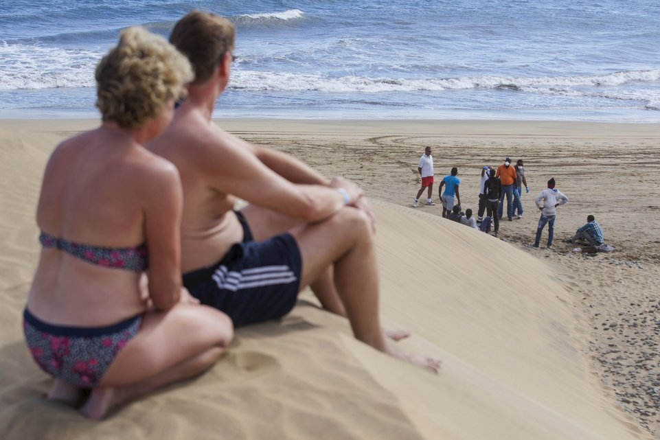 "Tourists look at would-be immigrants at the Maspalomas beach, on Gran Canaria in Spain's Canary Islands, in this November 5, 2014 file photo. Italy stepped up calls for a change to European asylum rules on Sunday as neighbouring states tightened border controls, turning back African migrants and leaving hundreds stranded at the frontier in northern Italy.  REUTERS/Borja Suarez/Files ATTENTION EDITORS - THIS PICTURE IS PART OF THE PACKAGE ""IN PLAIN SIGHT"". TO FIND ALL 9 IMAGES SEARCH 'MIGRANT EUROPEAN'.      TPX IMAGES OF THE DAY"