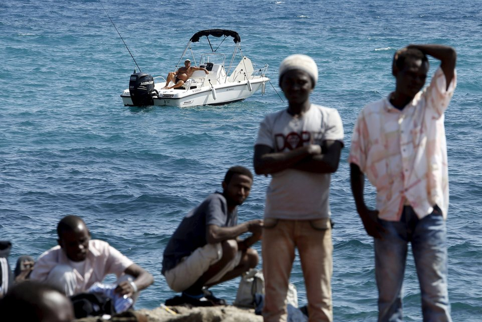 "A man fishes from his boat as a group of migrants gather on the seawall at the Saint Ludovic border crossing on the Mediterranean Sea between Vintimille, Italy and Menton, France, in this June 14, 2015 file photo. Italy stepped up calls for a change to European asylum rules on Sunday as neighbouring states tightened border controls, turning back African migrants and leaving hundreds stranded at the frontier in northern Italy.  REUTERS/Eric Gaillard/Files ATTENTION EDITORS - THIS PICTURE IS PART OF THE PACKAGE ""IN PLAIN SIGHT"". TO FIND ALL 9 IMAGES SEARCH 'MIGRANT EUROPEAN'.      TPX IMAGES OF THE DAY"