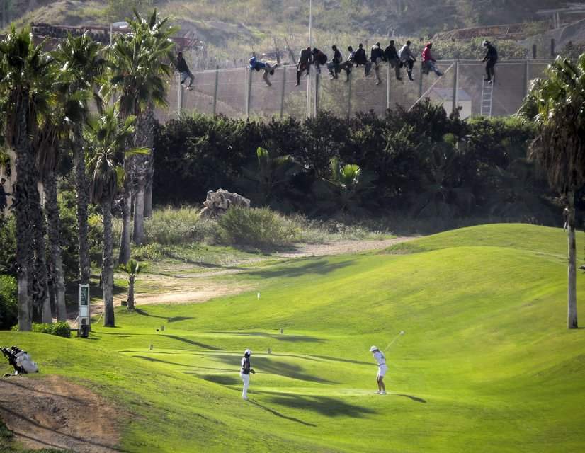 "A golfer hits a tee shot as African migrants sit atop a border fence during an attempt to cross into Spanish territories between Morocco and Spain's north African enclave of Melilla, in this October 22, 2014 file photo. Italy stepped up calls for a change to European asylum rules on Sunday as neighbouring states tightened border controls, turning back African migrants and leaving hundreds stranded at the frontier in northern Italy.  REUTERS/Jose Palazon/Files ATTENTION EDITORS - THIS PICTURE IS PART OF THE PACKAGE ""IN PLAIN SIGHT"". TO FIND ALL 9 IMAGES SEARCH 'MIGRANT EUROPEAN'."