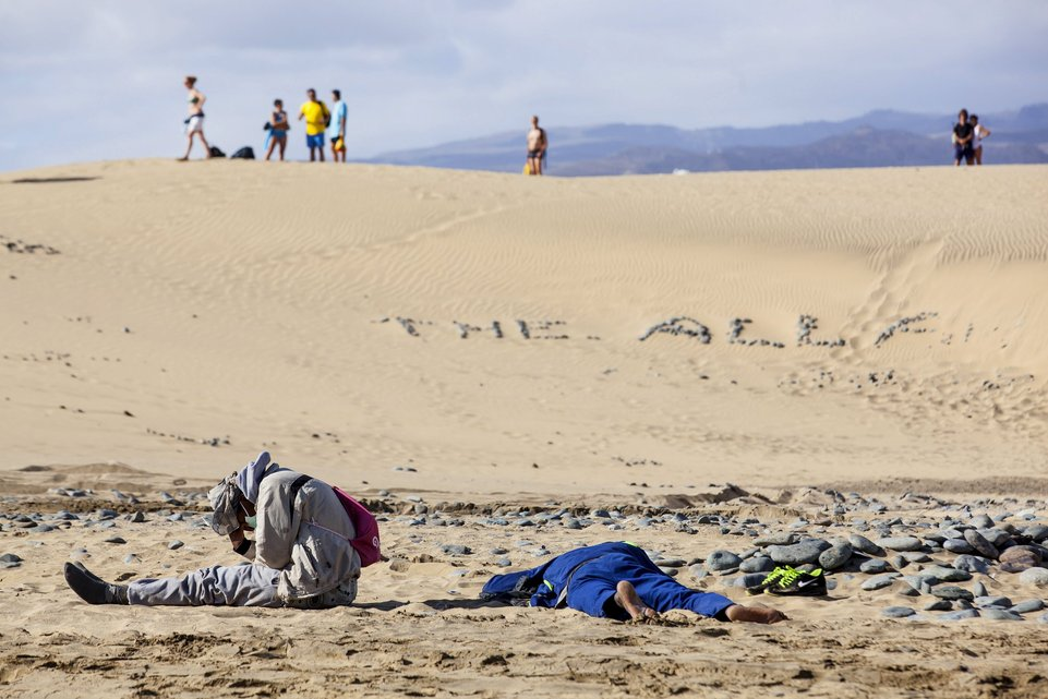 "Two would-be immigrants rest at Maspalomas beach on Gran Canaria in Spain's Canary Islands in this November 5, 2014 file photo. Italy stepped up calls for a change to European asylum rules on Sunday as neighbouring states tightened border controls, turning back African migrants and leaving hundreds stranded at the frontier in northern Italy.  REUTERS/Borja Suarez/Files ATTENTION EDITORS - THIS PICTURE IS PART OF THE PACKAGE ""IN PLAIN SIGHT"". TO FIND ALL 9 IMAGES SEARCH 'MIGRANT EUROPEAN'."