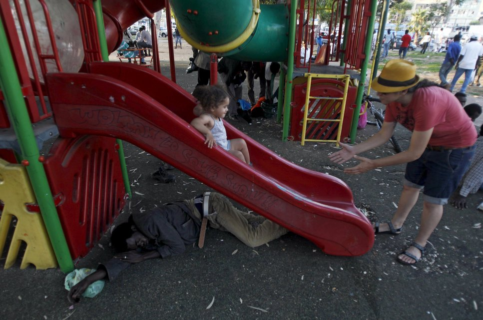 "A Sudanese migrant sleeps under a slide as an Israeli girl slides down it at Levinsky park in South Tel Avi, in this June 16, 2012 file photo. Italy stepped up calls for a change to European asylum rules on Sunday as neighbouring states tightened border controls, turning back African migrants and leaving hundreds stranded at the frontier in northern Italy.  REUTERS/Baz Ratner/Files ATTENTION EDITORS - THIS PICTURE IS PART OF THE PACKAGE ""IN PLAIN SIGHT"". TO FIND ALL 9 IMAGES SEARCH 'MIGRANT EUROPEAN'."