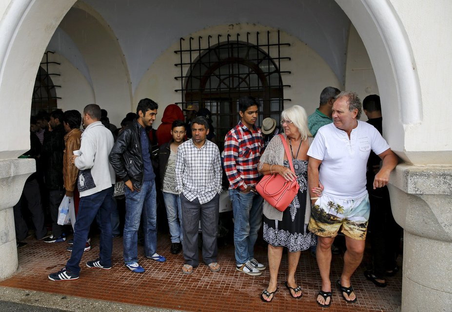 "A tourist couple (R) and a group of temporarily detained immigrants take shelter from rain outside a police station in Kos island, Greece, in this May 29, 2015 file photo.  Italy stepped up calls for a change to European asylum rules on Sunday as neighbouring states tightened border controls, turning back African migrants and leaving hundreds stranded at the frontier in northern Italy.  REUTERS/Yannis Behrakis/Files ATTENTION EDITORS - THIS PICTURE IS PART OF THE PACKAGE ""IN PLAIN SIGHT"". TO FIND ALL 9 IMAGES SEARCH 'MIGRANT EUROPEAN'."