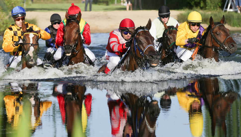 Horses with first placed horseman Cevin Chan (L) on his horse Kazzio cross a lake in Hamburg's district Horn during the so-called Alpine Motorenoel-Seejagdrennen as a part of Hamburg Derby-Meeting 2015 near the racetrack in Hamburg - Horn, northern Germany, on June 30, 2015.  AFP PHOTO / DPA / AXEL HEIMKEN +++ GERMANY OUT