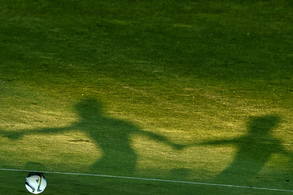 This picture taken on August 10, 2015 at the Boris Paichadze Dinamo Arena in Tbilisi shows shadows of Sevilla FC players as they attend a training session on the eve of the UEFA Super Cup football match between FC Barcelona and Sevilla FC. AFP PHOTO / KIRILL KUDRYAVTSEV