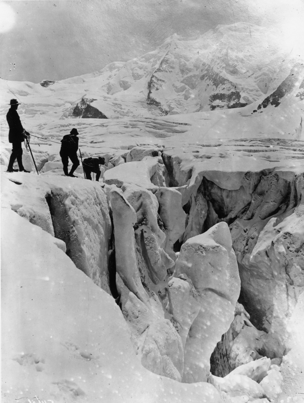 December 1910:  Three mountaineers crossing a crevsasse on the Pers Glacier in the Alps.  (Photo by Topical Press Agency/Getty Images)
