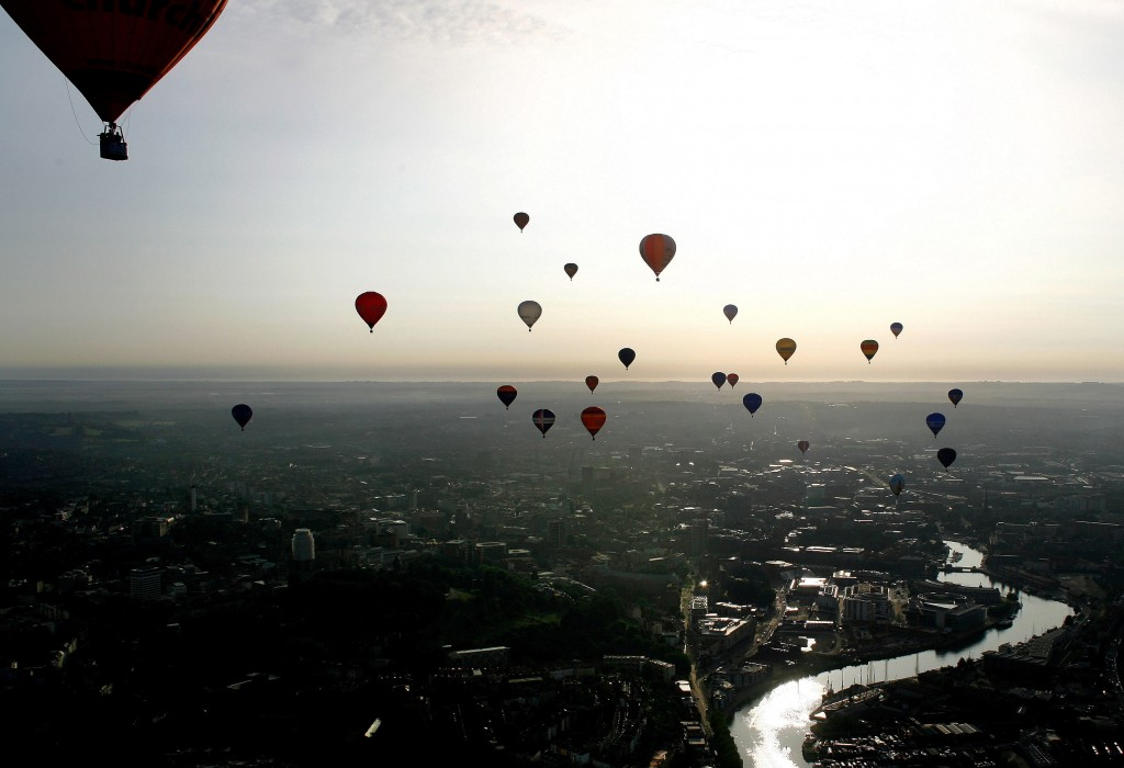 Balloons fly across the Bristol city centre during the 2006 Bristol International Balloon Fiesta in southwest England August 8, 2006. The four day annual event includes concerts and mass balloon launches.     REUTERS/Kieran Doherty  (BRITAIN) - RTR1G78V