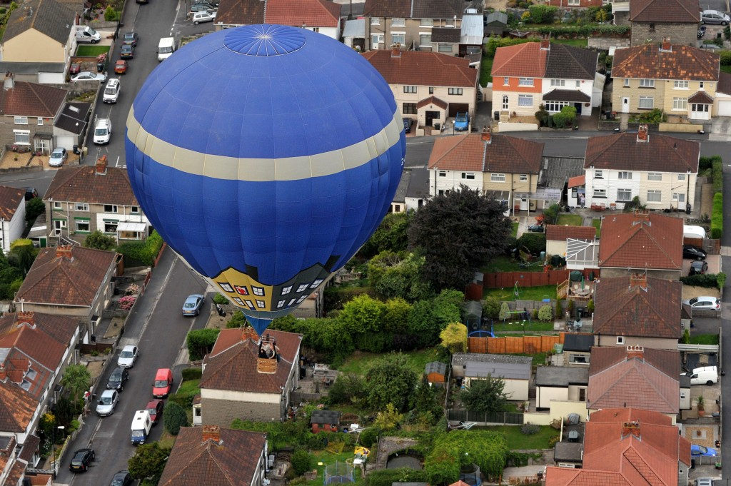 A hot air balloon flies above a residential area of Bristol, south-west England, on August 13, 2010, during a mass assent flight at the 32nd Bristol International Balloon Fiesta in Bristol, south-west England, on August 13, 2010. Weird and wonderful shapes filled the skies as Europe's biggest hot air balloon festival marked the golden jubilee of modern ballooning. More than half a million people were expected to attend the four-day Bristol International Balloon Fiesta, held on a country estate in Bristol, southwest England. AFP PHOTO/BEN STANSALL