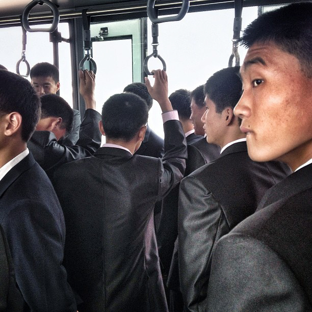 North Korean men on an airport transport bus headed to the Air Koryo flight for Beijing. (AP Photo/David Guttenfelder)