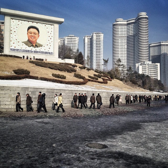 Residents of Pyongyang walk by a mosaic of the late leader Kim Jong Il in the 2nd anniversary if his death. (AP Photo/David Guttenfelder)