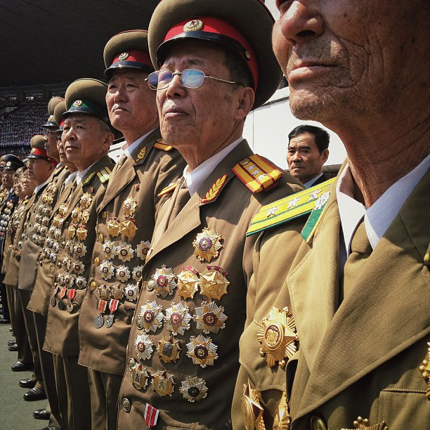 Chests festooned with medals, North Korean retired military members stand at attention in Pyongyang. (AP Photo/David Guttenfelder)