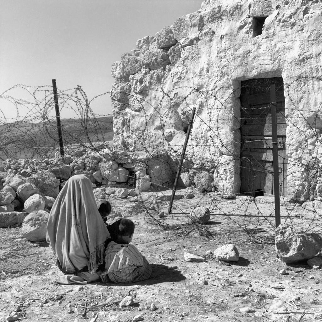 UNRWA Archive - Ausstellung Photobastei - BILDSEITE Eine palästinensische Flüchtlingsfrau, die 1949 von der Waffenstillstandslinie (Grüne Linie) von ihrem Haus abgeschnitten wurde. Die Waffenstillstandslinie wurde 1948 nach dem Arabisch-Israelischen Krieg errichtet. Nicht datiert © UNRWA-Archiv, Fotograf unbekannt