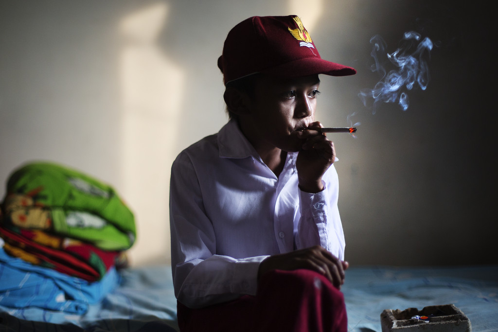 Ilham Hadi, who has smoked up to two packs a day, poses for a photo wearing his third grade uniform while smoking in his bedroom on February 14, 2014. (Photo By: Michelle Siu)