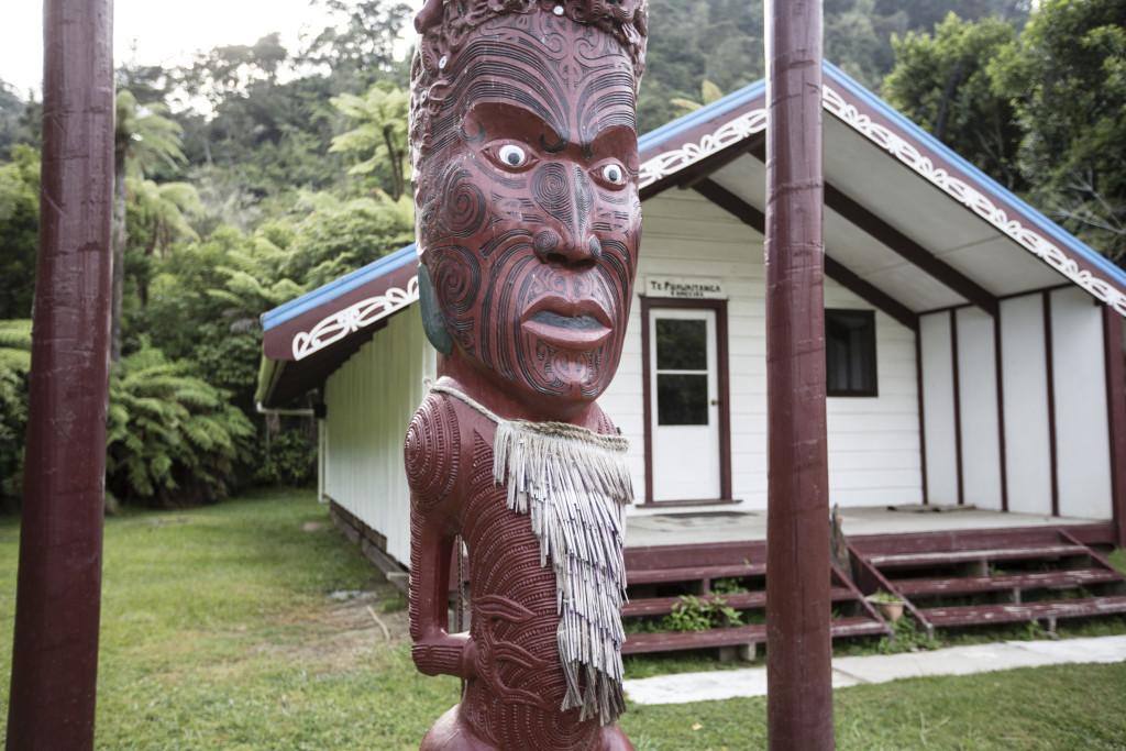 Tieke Kainga heisst der 3. Zeltplatz. Er befindet sich auf dem Gelände eines Maori Kultplatzes, genannt Marae. Der geschnitzte Pfahl (Pou Whenua) markiert die territorialen Ansprüche des Tieke Kainga Volkes. Kanu Trekking auf dem Whanganui River, Nordinsel, Neuseeland, Foto: Bernard van Dierendonck