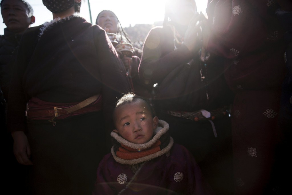 A boy joins other ethnic Tibetan people in praying as the sun comes out from behind the hill above a Buddhist laymen lodge where thousands of monks and nuns gather for morning chanting session during the Utmost Bliss Dharma Assembly, the last of the four Dharma assemblies at Larung Wuming Buddhist Institute in remote Sertar county, Garze Tibetan Autonomous Prefecture, Sichuan province, China November 1, 2015. The eight-day gathering of people chanting mantras and listening to teachings of monks starts every year around the 22rd of the ninth month on Tibetan calendar, the great day of BuddhaÕs Descending from Tushita Heavens. The Larung Wuming Buddhist Institute, located some 3700 to 4000 metres above the sea level was founded in 1980 by Khenpo Jigme Phuntsok, an influential lama of Nyingma sect of Tibetan buddhism with only around 30 students but is now widely known as one of the biggest centres to study Tibetan Buddhism in the world. Picture taken November 1, 2015. REUTERS/Damir Sagolj