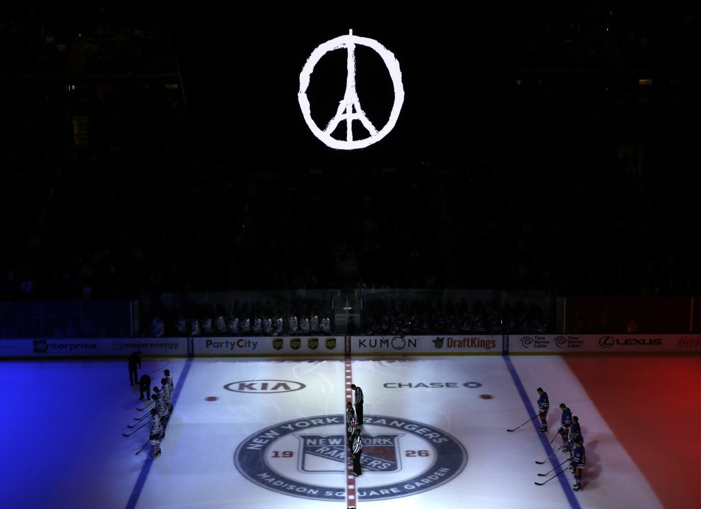 The colors of France's flag are projected onto the ice as the national anthem of France is played before an NHL hockey game between the New York Rangers and the Toronto Maple Leafs, Sunday, Nov. 15, 2015, in New York. Multiple attacks across Paris on Friday night left scores dead and hundreds injured. (AP Photo/Seth Wenig)