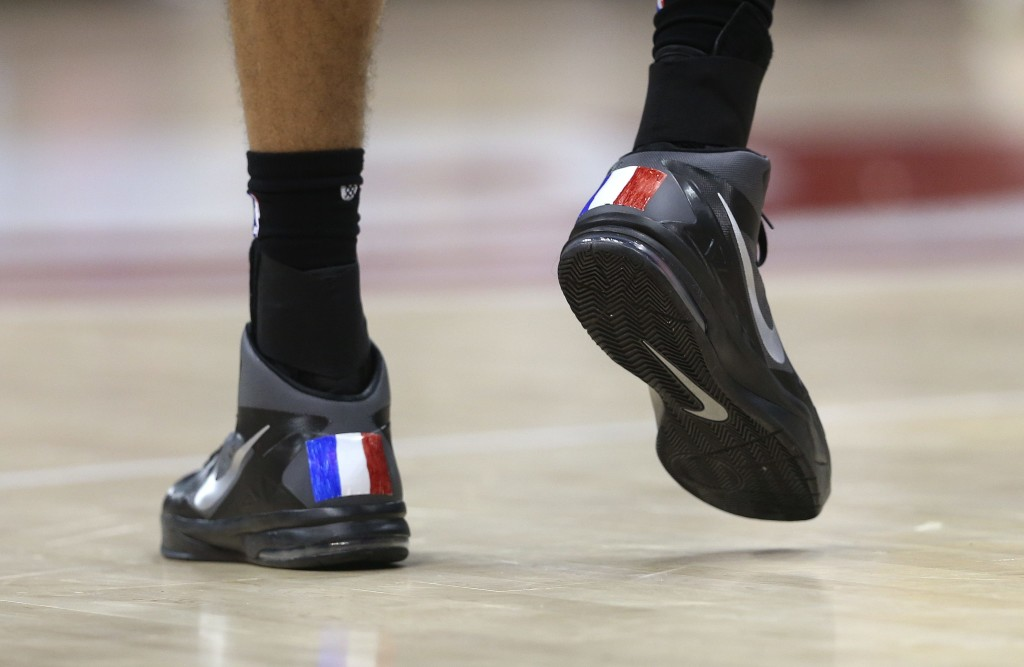 Utah Jazz center Rudy Gobert (27), of France, wears shoes decorated with French flags in the second half of an NBA basketball game against the Atlanta Hawks, Sunday, Nov. 15, 2015, in Atlanta. Utah won 97-96. (AP Photo/John Bazemore)