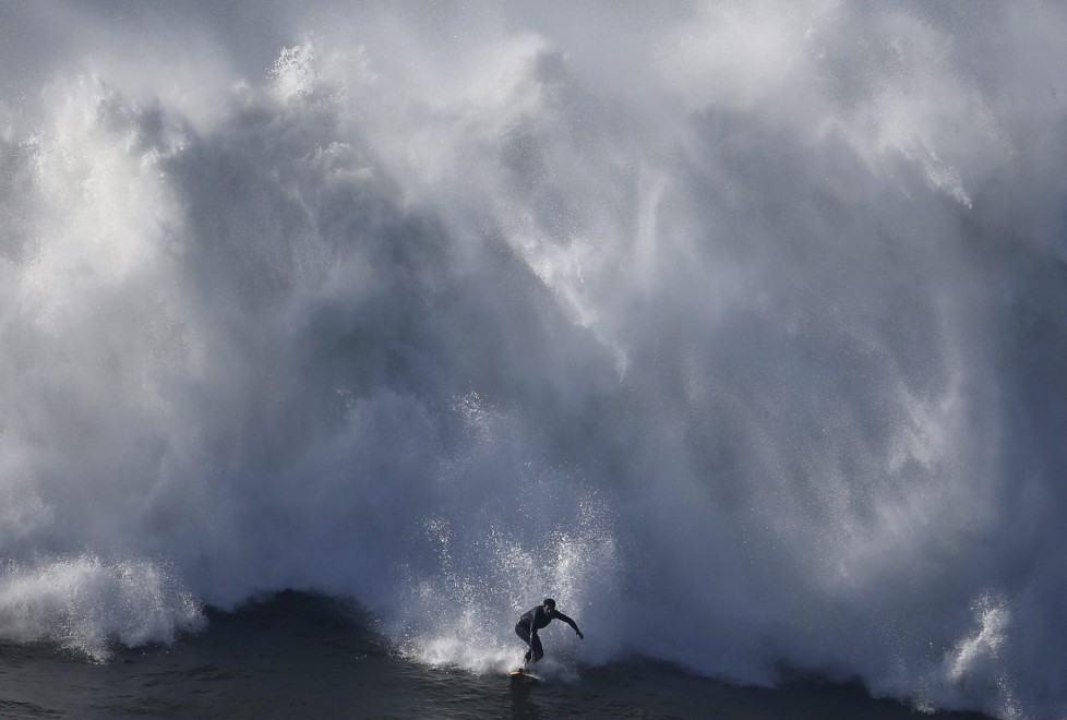 A surfer drops in on a large wave at Praia do Norte in Nazare, Portugal, November 29, 2015. The Praia do Norte beach has become a famous beach for big waves surfers around the world since Hawaiian surfer Garrett McNamara's world record for the largest wave surfed in 2011. REUTERS/Rafael Marchante