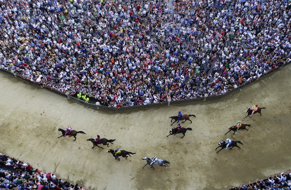 Horses race during the general practice session for the Palio di Siena horse race in Siena, Italy, July 1, 2015. Each July 2 and August 16, almost without fail since the mid-1600s, 10 riders have hurtled bareback around Siena's shell-shaped central square in a desperate bid to win the Palio, a silk banner depicting the Madonna and child. REUTERS/ Max Rossi TPX IMAGES OF THE DAY ATTENTION EDITORS - FOR EDITORIAL USE ONLY. NOT FOR SALE FOR MARKETING OR ADVERTISING CAMPAIGNS. - RTX1INO4