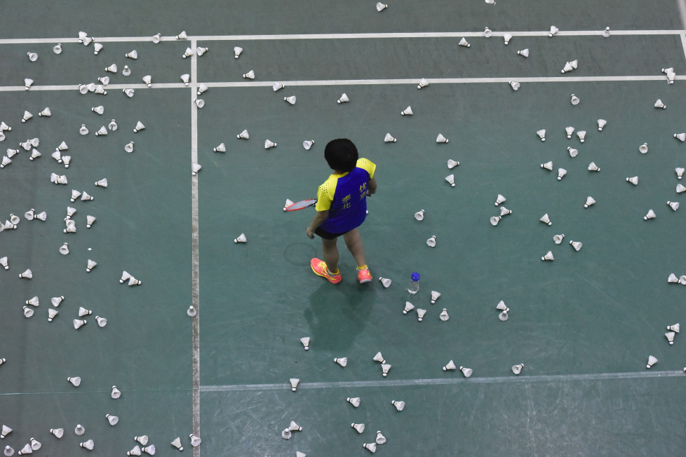 This photo taken on January 6, 2016 shows a player walking amongst shuttlecocks during a training session with the Beijing Badminton team in Beijing. AFP PHOTO / FRED DUFOUR / AFP / FRED DUFOUR
