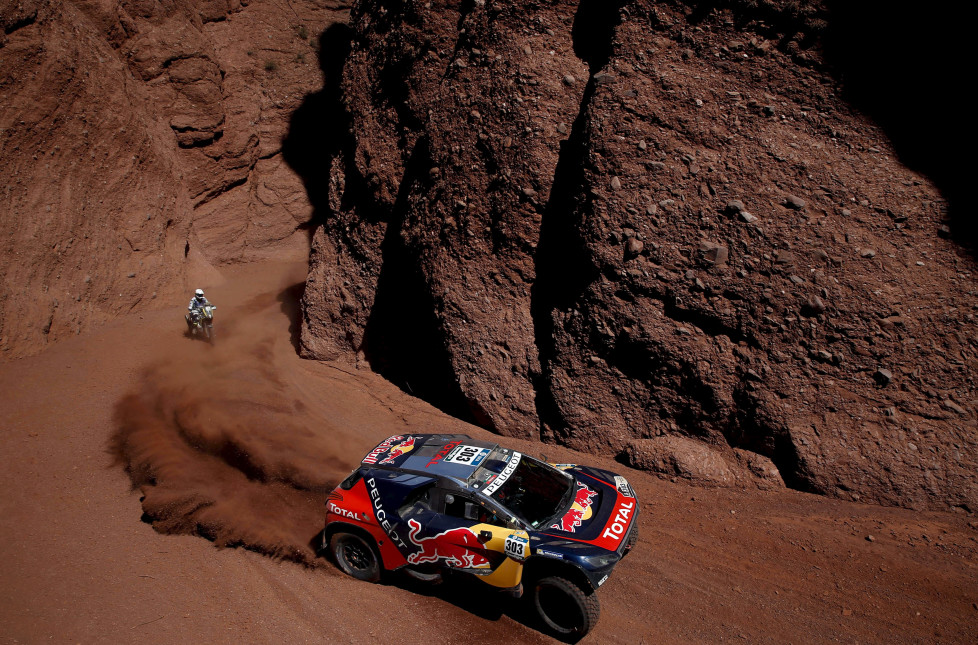 Carlos Sainz of Spain drives his Peugeot past Hans Smit of Netherlands on his Husqvarna motorcycle during the eighth stage in the Dakar Rally 2016 near Cafayate, Argentina, January 11, 2016. REUTERS/Marcos Brindicci TPX IMAGES OF THE DAY - RTX21XI9