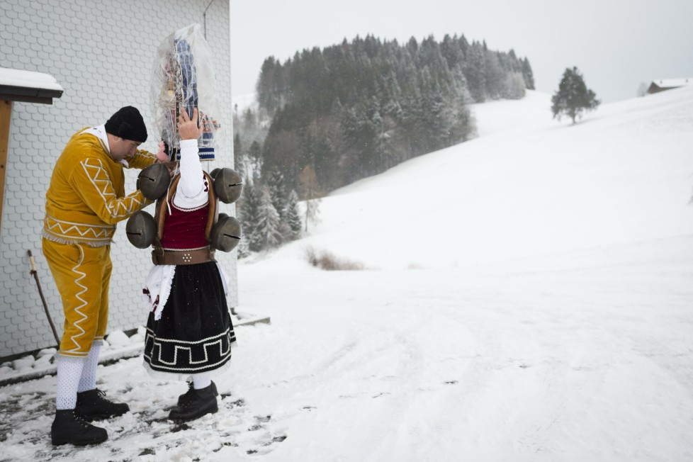 """Mario Hasler, links, hilft Ernst Alder von der Schoenen Chlausschuppel """"Oese Schuppel"""" in die Tracht, am Mittwoch, 13. Januar 2016, am alten Silvester in Waldstatt. Die Chlaeuse starten frueh morgens und wandern von Hof zu Hof bis spaet in die Nacht, um den Bewohnern ein Gutes Neues Jahr zu wuenschen. Traditionell werden die Chlaeuse mit Weiss- oder Gluehwein bedient. (KEYSTONE/Gian Ehrenzeller) So-called Silvesterchlaeuse (New Years Clauses) dress up in Waldstatt, Switzerland, Wednesday, January 13, 2016, to offer their best wishes for the New Year (following the Julian calendar) to the farmers in this region. After their performance of singing and dancing the Silvesterchlaeuse receive hot drinks. (KEYSTONE/Gian Ehrenzeller)"""
