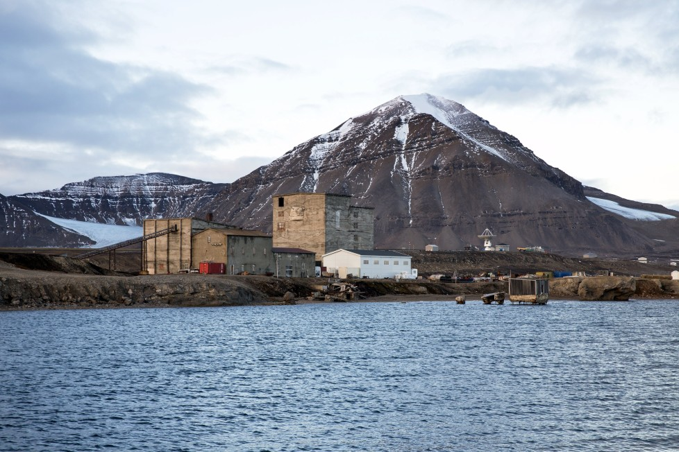 """Warehouses and the old part of the Ny-Alesund, Norway settlement from the coal mining period which closed in 1963, are seen October 11, 2015. A Norwegian chain of islands just 1,200 km (750 miles) from the North Pole is trying to promote new technologies, tourism and scientific research in a shift from high-polluting coal mining that has been a backbone of the remote economy for decades. Norway suspended most coal mining on the Svalbard archipelago last year because of the high costs, and is looking for alternative jobs for about 2,200 inhabitants on islands where polar bears roam. Part of the answer may be to boost science: in Ny-Alesund, the world's most northerly permanent non-military settlement, scientists from 11 nations including Norway, Germany, France, Britain, India and South Korea study issues such as climate change. The presence of Norway, a NATO member, also gives the alliance a strategic foothold in the far north, of increasing importance after neighbouring Russia annexed Ukraine's Crimea region in 2014. REUTERS/Anna FilipovaPICTURE 15 OF 19 - SEARCH """"SVALBARD FILIPOVA"""" FOR ALL IMAGES"""