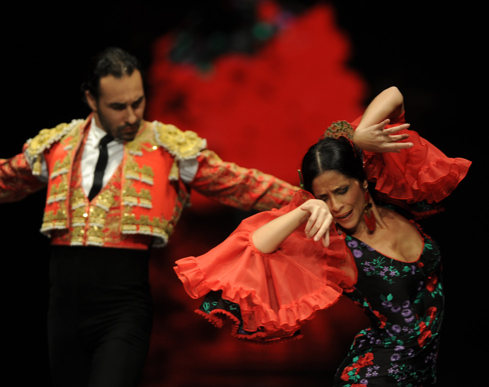 Flamenco dancers Cristina Gallego (R) and Jose Vidal (L) present creations by Carmen Latorre during the SIMOF 2016 (International Flamenco Fashion Show) in Sevilla, on February 6, 2016. AFP PHOTO/ CRISTINA QUICLER / AFP / CRISTINA QUICLER