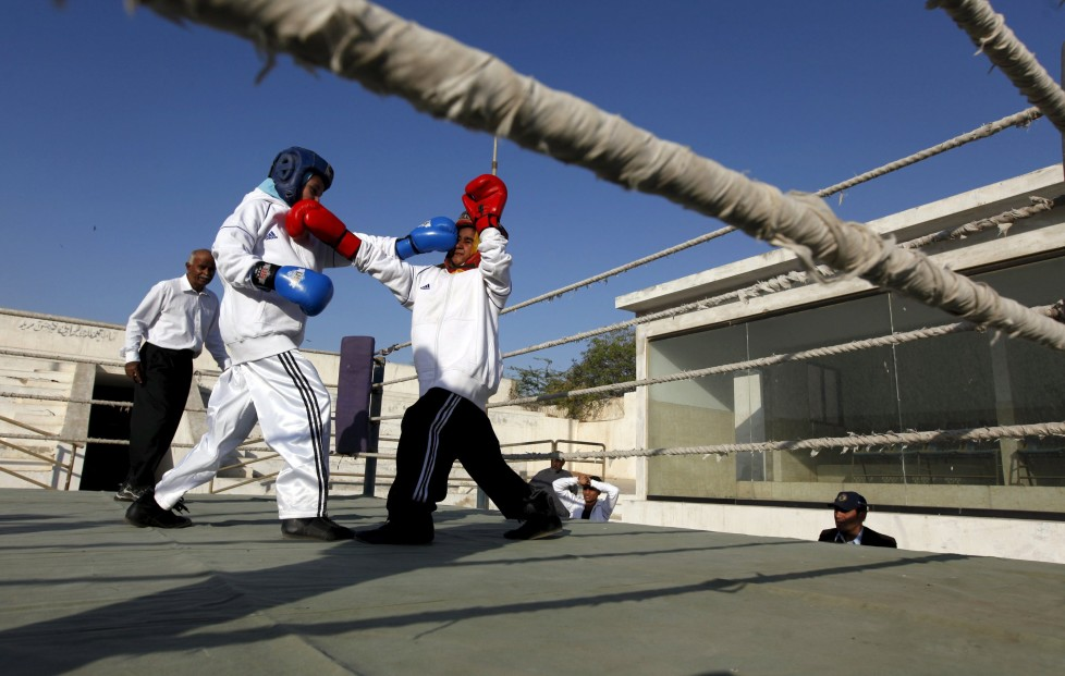 """Tabia (L), 12, fights against Aamna, 11, during the Sindh Junior Sports Association Boxing Tournament in Karachi, Pakistan February 21, 2016. For the past six months about a dozen girls, aged 8 to 17, have gone to the Pak Shine Boxing Club after school to practice their jabs, hooks and upper cuts. Pakistani women have been training as boxers in small numbers and competed in the South Asian Games last year, said Younis Qambrani, the coach who founded the club in 1992 in the Karachi neighbourhood of Lyari, better known for internecine gang warfare than for breaking glass ceilings. REUTERS/Akhtar Soomro SEARCH """"THE WIDER IMAGE"""" FOR ALL STORIES"""